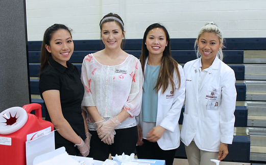 four students working at a community health fair