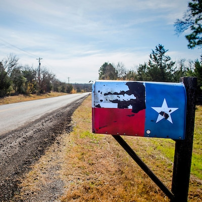 Texas flag mailbox along a farm road